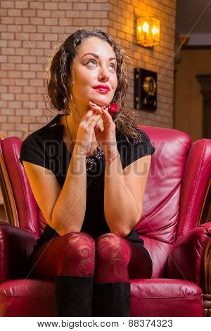 Portrait of beautiful romantic brunette on a red chair. Professional make-up on a beautiful woman.