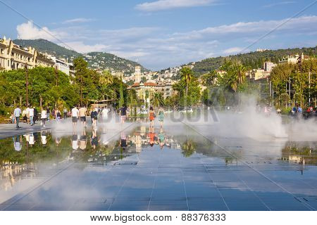 NICE, FRANCE - OCTOBER 2, 2014: People walking through soaking fountain on Promenade du Paillon reflecting the city and surrounding hills.