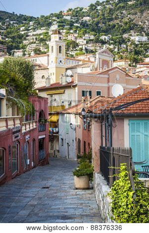 VILLEFRANCHE-SUR-MER, FRANCE - OCTOBER 4, 2014: Cobblestone street with colourful buildings leads to the heart of old town and Eglise Saint-Michel (Saint Michael's Church).