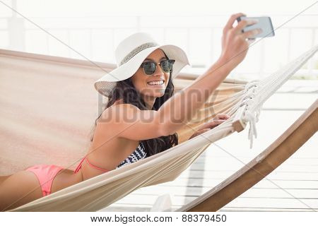 Pretty brunette relaxing on a hammock and taking selfie in patio