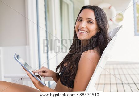 Beautiful young woman relaxing and using tablet pc on sun lounger