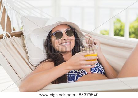 Pretty brunette relaxing on a hammock and drinking orange juice in patio