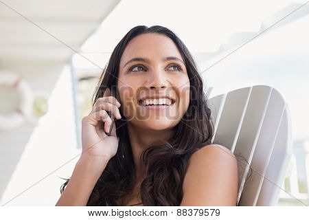 Pretty brunette sitting on a chair and calling with her mobile phone in patio