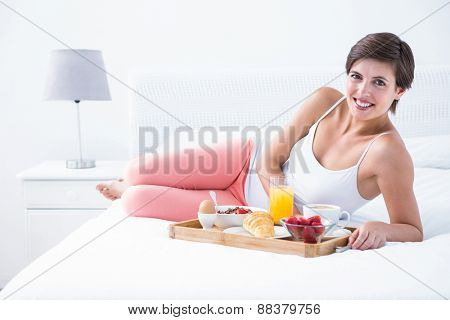 Happy brunette having her breakfast in bed at home in he bedroom