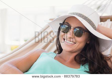 Pretty brunette relaxing on a hammock in patio