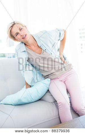 Blonde woman having backache in the living room