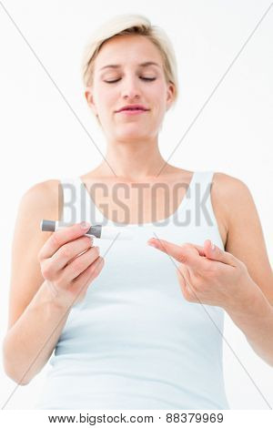 Smiling woman testing her blood glucose level on white background