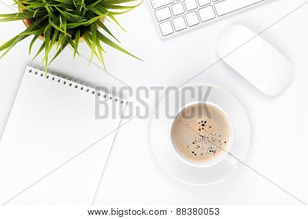 Office desk table with computer, supplies, coffee cup and flower. Top view with copy space