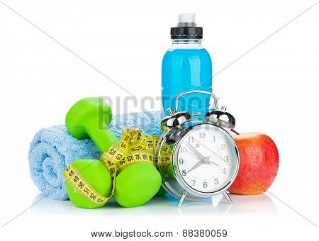 Two green dumbells, tape measure, healthy food and alarm clock. Fitness and health. Isolated on white background