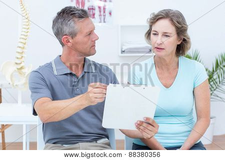 Physiotherapist showing his notes to his patient in medical office