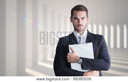 Businessman in suit posing with his laptop against curved white room
