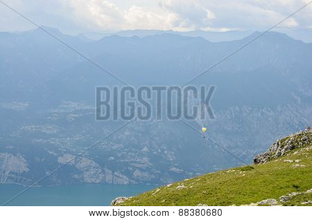 Paraglider Is Flying In Front Of Mountain Landscape Of Alps - Monte Baldo