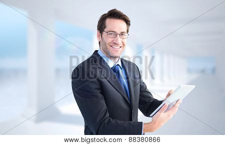 Businessman looking at the camera while using his tablet against bright white room with columns