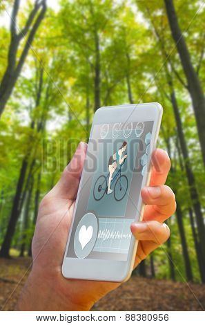 hand holding smartphone against lush trees in the forest