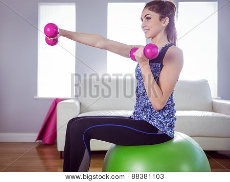 Fit woman lifting dumbbells on exercise ball at home in the living room