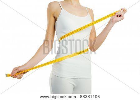 Slim woman measuring her waist on white background