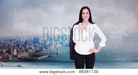 Pretty businesswoman smiling at camera against city scene in a room