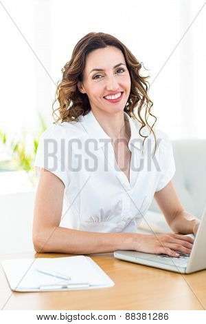 Smiling businesswoman working with her laptop on white background