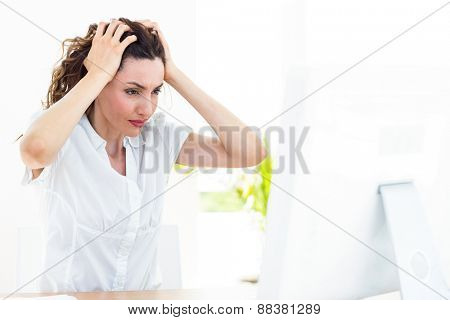 Upset businesswoman sitting at her desk on white background