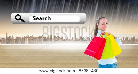 Smiling blonde holding shopping bags against city on the horizon
