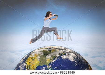 Cheerful classy businesswoman jumping while holding binoculars against white clouds under blue sky