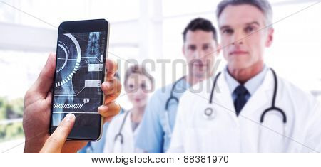 hand holding smartphone against serious medical team in row