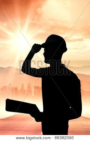 Manual worker wearing hardhat while holding clipboard against sun shining over road and city