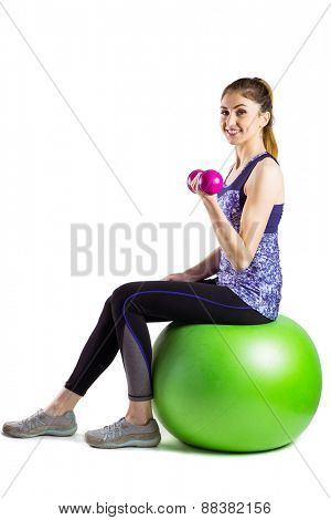 Fit woman lifting dumbbell sitting on ball on white background