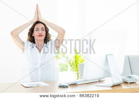 Relaxed businesswoman doing yoga on white background