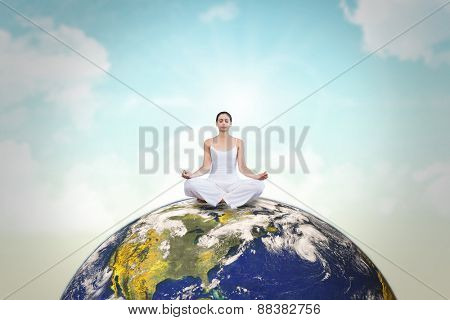 Peaceful woman in white sitting in lotus pose against blue sky