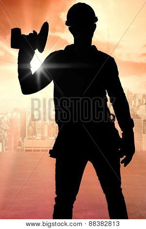 Handyman wearing tool belt while holding power drill against sun shining over road and city
