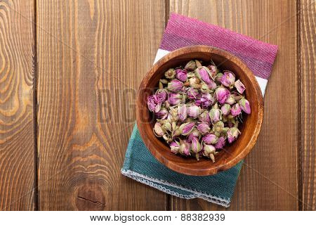 Rose flavour spice in wooden bowl on table with copy space