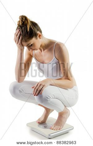 Slim woman disappointed on scales on white background