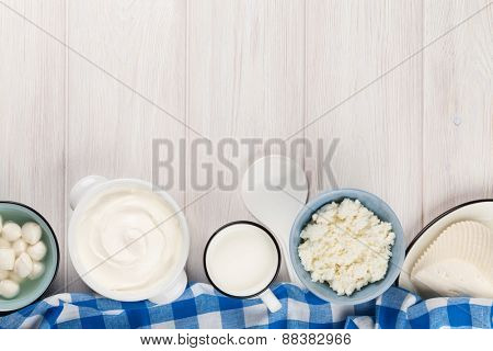 Dairy products on wooden table. Sour cream, milk, cheese, yogurt and butter. Top view with copy space