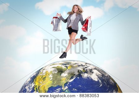 Festive blonde jumping with shopping bags against blue sky
