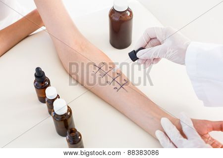 Doctor doing skin prick test at her patient in medical office