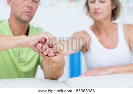 Doctor examining his patients hand in medical office