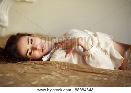 Sensual Young Woman Thoughtfully Lying On The Bed At Home In Sunny Daylight