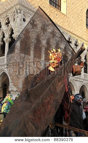 Masked Person In Costume On San Marco Square Near Doge's Palace During The Carnival In Venice