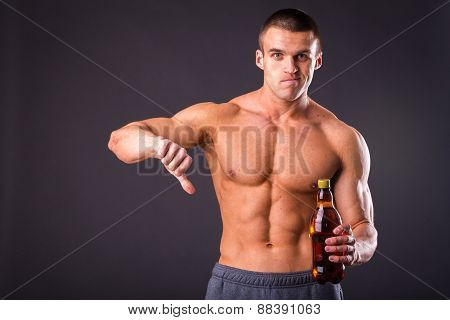 Male bodybuilder shows that beer is bad.