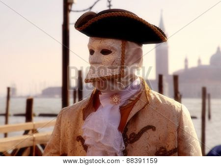 Masked Person In Costume On Pier In St. Mark's Square During The Carnival Of Venice