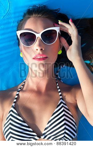 Colorful summer portrait of young attractive brunette woman wearing sunglasses lying down at the swimming pool