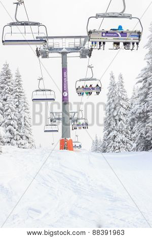 Ski Lift In Mountain With Skies And Snowboards People