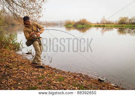 Young fisherman fishing on the river bank