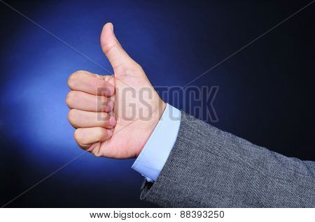 closeup of the hand of a young caucasian businessman wearing a grey suit giving a thumbs-up sign on a black background lightened in blue