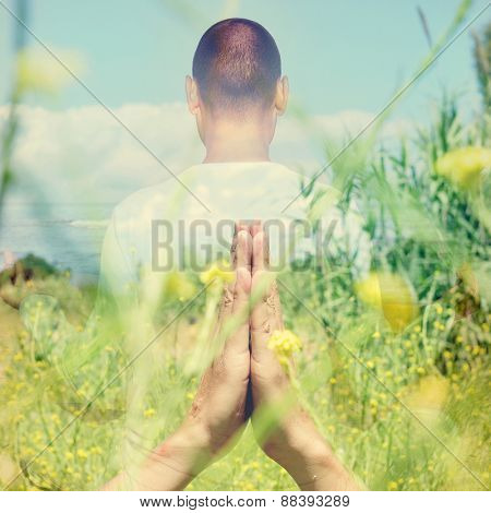 double exposure of a young caucasian yogi man in meditating outdoors with his hands in anjali mudra