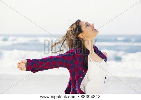 Beautiful and happy teen at the beach enjoying the summer