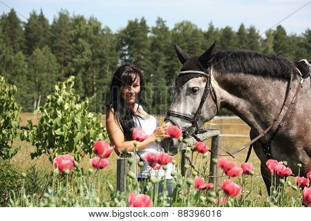 Beautiful Woman In The Blooming Garden With Horse