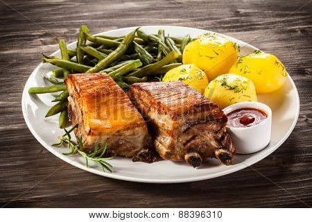Grilled ribs, boiled potatoes and vegetables