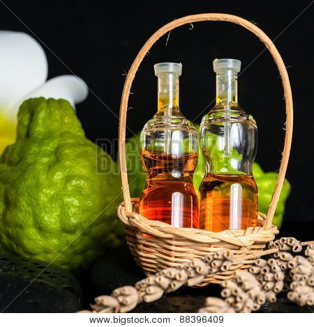 Aromatic Spa Concept Of Bottles Essential Oil In Basket, Flower, Bergamot, Candles And Black Zen Bas